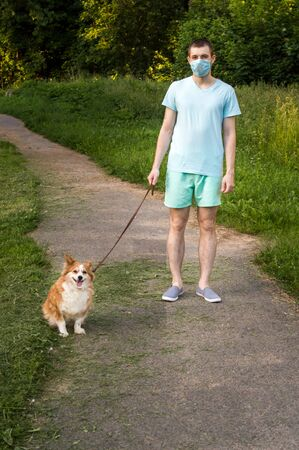 young man walks with a dog in a medical mask in the park alone. Vertical photo. Portrait Imagens