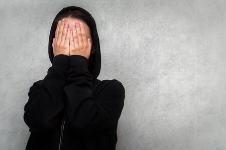 young woman in a black sweater and a hood on her head covers her face with her hands. The concept of mental health. Depression Stress Negative emotion.