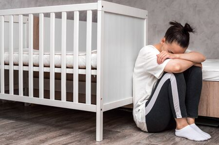 young woman sits sad by the crib. Postpartum depression concept