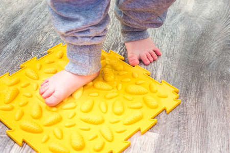 Child's feet on the orthopedic mat close-up. Valgus concept Banco de Imagens