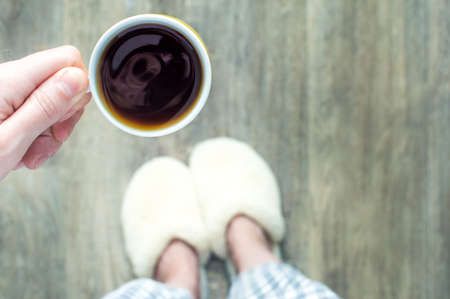 woman in slippers holds a cup of coffee in her hands. Morning concept