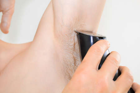 Armpit shaving with a trimmer Stock Photo