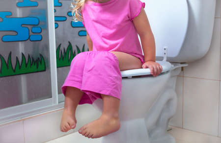 Baby sitting at the toilet Stock Photo