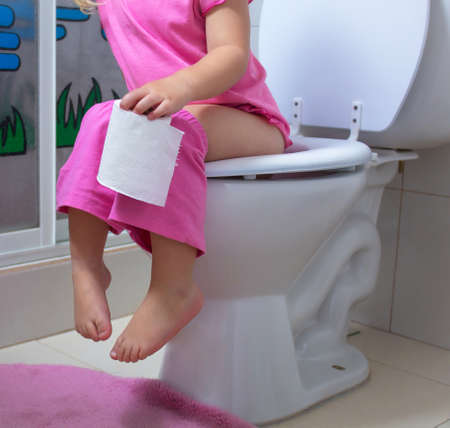 A child is sitting on the toilet
