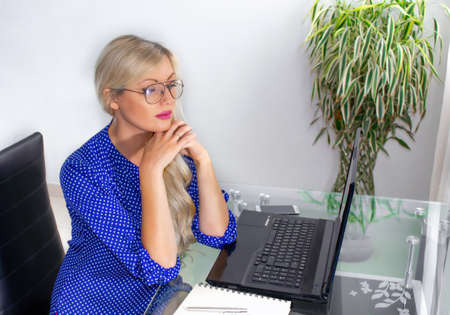 Woman sitting behind the desk at work Фото со стока