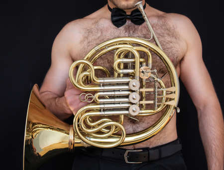 Tough naked musician wearing a bowtie