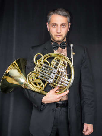 Musician without shirt and his french horn Фото со стока