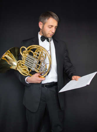Well dressed man with a French horn Фото со стока