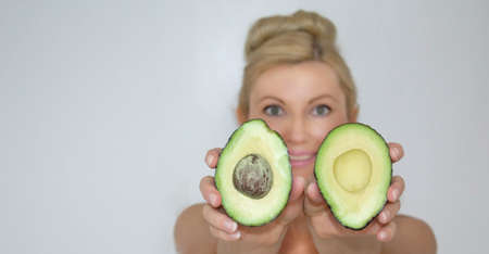 Smiling woman holds cutted avocado