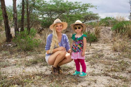 Woman wearing a hat walking with kid