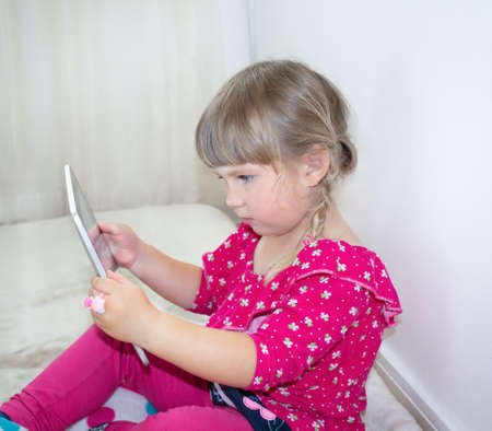 Little girl looking at the tablet computer Фото со стока