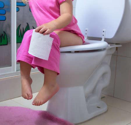 Kleines Mädchen, das ein Badezimmer benutzt
