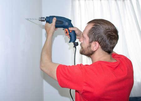 Man wearing red drilling a wall Фото со стока