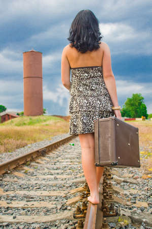 The girl on rails with a suitcase Stock Photo - 10159592