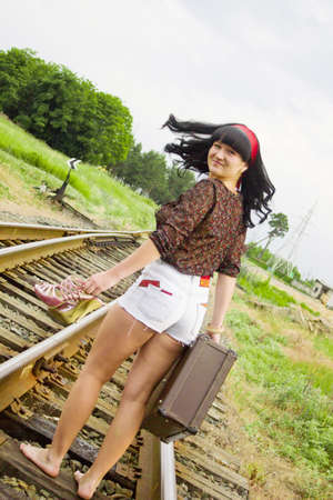 The girl on rails with a suitcase photo