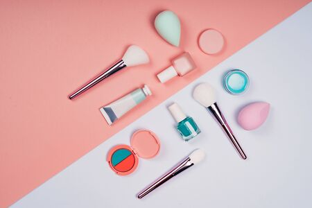 Makeup products on color background.