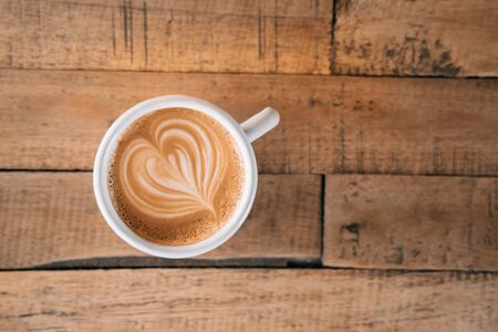 Cup of coffee with latte art in the wooden space background.