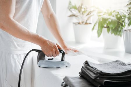 Man ironing bed linen on iron board with steam generator at home. Housework and household concept.