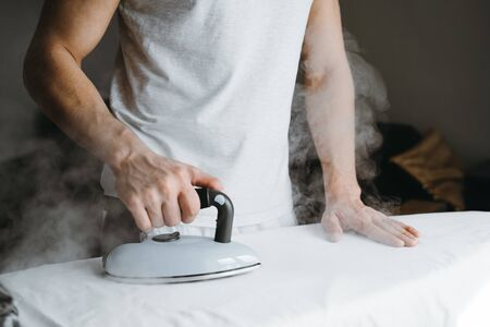 Man ironing bed linen on iron board at home.