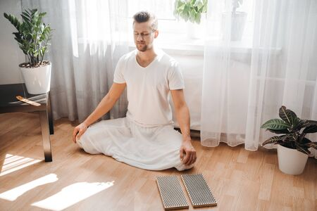 Young man meditating, sitting in the lotus position.