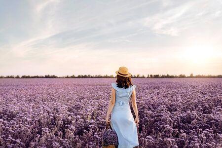 Woman in purple flowers field at sunset in blue dress.