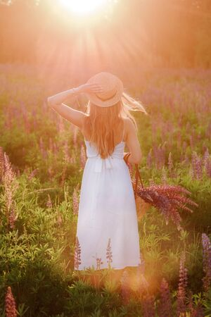 Girl with long hair standing with his back at sunset with a large bouquet of lupins.