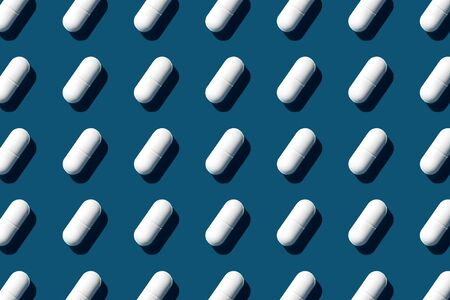 Trendy pattern made with Pharmaceutical medicine white pills on dark blue background.