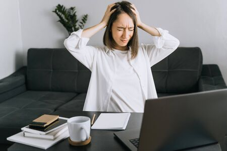 Portrait of tired young woman with laptop at the home office. Stock Photo