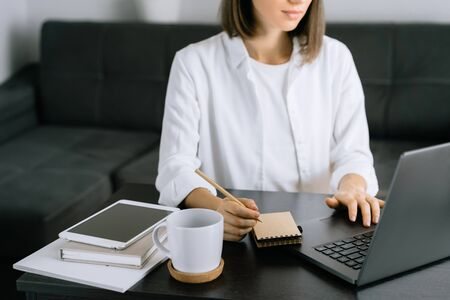 Woman using laptop at workplace in office
