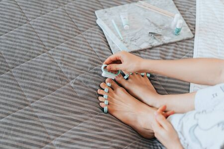 Girl makes a pedicure at home.