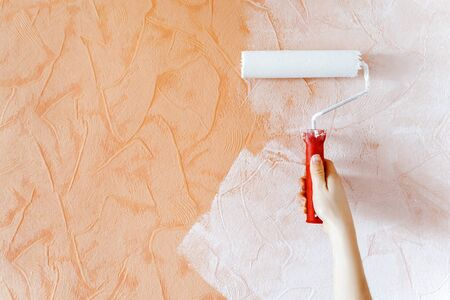 Woman hand painting a white color with a paint roller on orange wall. Self-made repair at home during quarantine and self-isolation. Standard-Bild