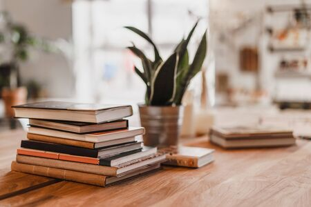 Stack of colorful books on wooden table in the room. Selective focus. Stock Photo