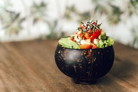 Poke bowl with tuna, avocado, vegetables and sesame on pattern background.