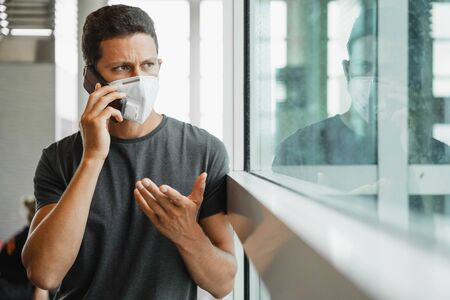 Men with respirator mask in airport talking on the phone. Stock Photo