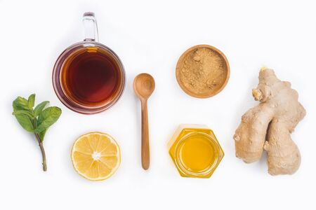 A glass cup of natural tea with ginger, lemon, mint and honey on white background.