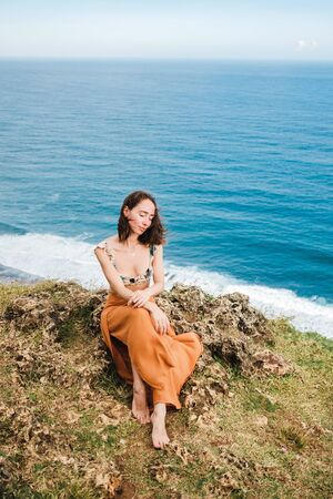 Young woman sitting on cliffs edge.