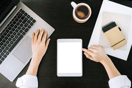 Top view mockup image of woman hands holding white tablet pc. White desktop screen with laptop and coffee cups on wooden black table at home or office.