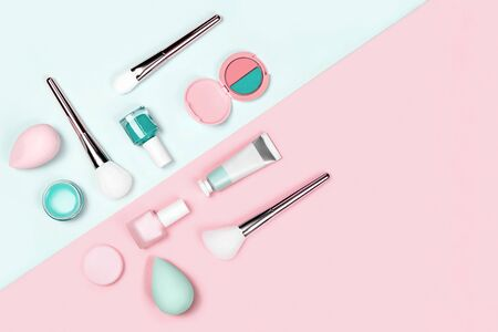 Makeup products with brushes, nail polish, eyeshadow, sponges, cream and lipstick on neo-mint and pink color background. Flat lay, top view, space for text. Stock Photo