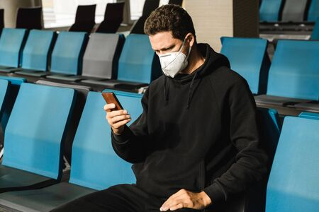 Man with respirator mask sitting in airport.