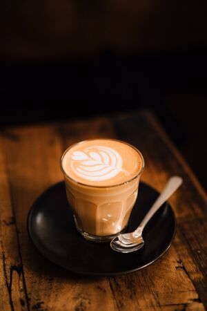 Mug of flat white coffee with latte art on wooden table.