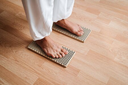 Close-up of unrecognizable brave man in white pants standing barefeet on bed of nails at morning yoga practice. Balance exercise, courage and patience.
