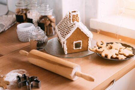 Homemade gingerbread house and cookies with rolling pin scene on wooden table in the kitchen, warm bokeh background.
