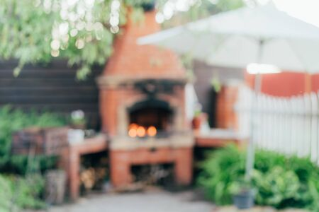 Defocused outdoor scene with back light representing outdoor cooking, summer gathering, BBQ, grill in the garden.