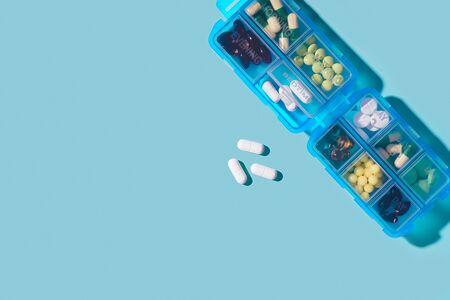 Prescription pills and vitamins in a blue pill box on neo mint color background. Flat lay photo, space for text.