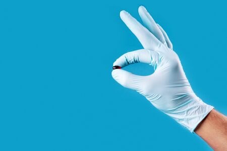 Small pill in the hand in medical gloved palm on neo mint color background. Concept of coronavirus and Covid-19. Stock Photo
