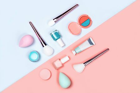 Makeup products with brushes, nail polish, sponges, eyeshadow, cream and lipstick on coral-blue color background. Flat lay, top view, space for text.