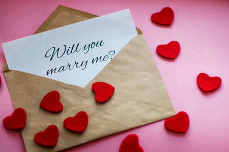 The envelope with a note Will you marry me? and carved hearts on pink background. Marriage proposal concept. Stock Photo
