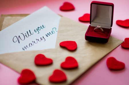 """Schöner Ehering mit Edelstein in einer roten Geschenkbox, geschnitzten Herzen und Umschlag mit der Aufschrift """"Willst du mich heiraten?"""" auf rosa Hintergrund. Heiratsantragskonzept."""