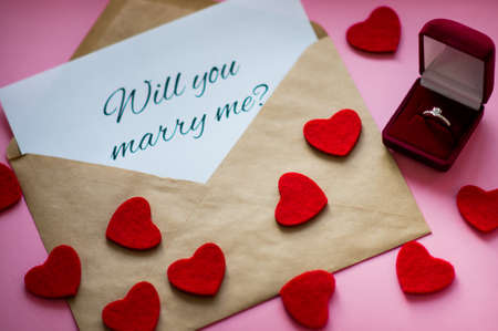 Beautiful shiny engaging ring with precious stone in a red gift box, carved hearts and envelope with a note Will you marry me? on pink background. Marriage proposal concept.