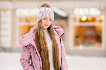 A girl in a pink warm jacket and hat on the background of golden yellow lights and blurred shop windows. Winter wonderland. Christmas and New Year concept.
